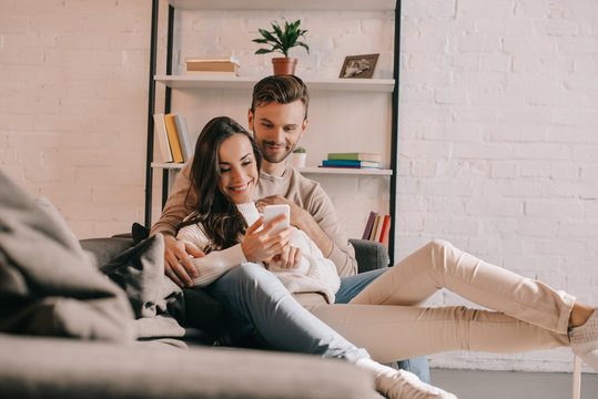 smiling young couple using smartphone together on couch at home
