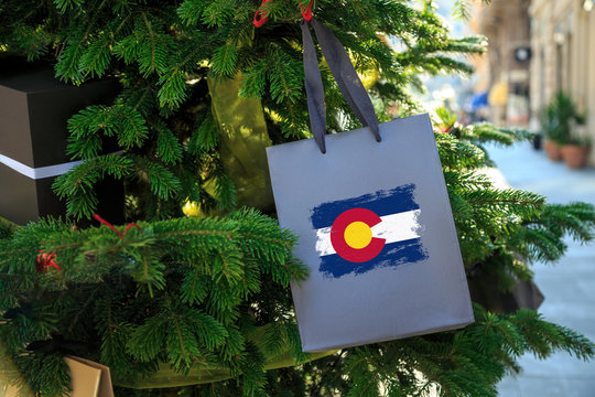 Colorado state flag printed on a Christmas gift box. Printed present box decorations on a Xmas tree branch on a street. Christmas shopping in United States, local market sale and deals concept.