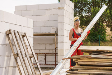 Woman carrying gutter on construction site