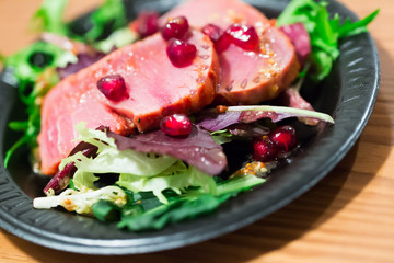 Slices of raw tuna with herbs and pomegranate