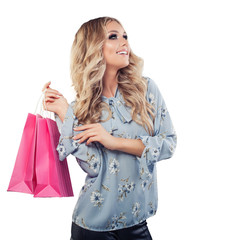 Happy young woman looking up and holding shopping bags isolated on white