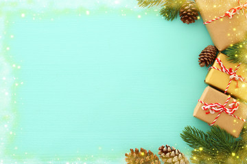 Christmas background with pine cones, fir branches and gifts over wooden white background. Flat lay, top view.