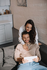 high angle view of happy young woman embracing her boyfriend from behind while he using tablet at home