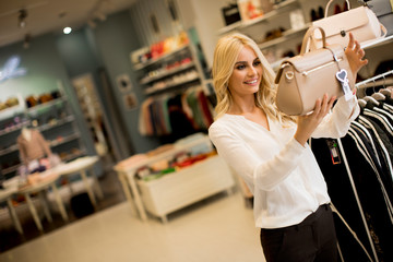 Young woman buying purse in the store
