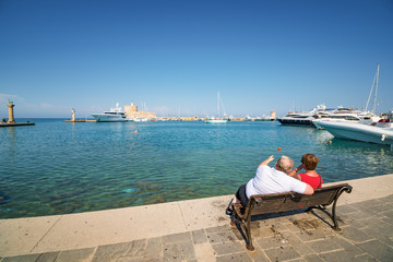Sitting couple looking at boats in Mandraki harbor in City of Rhodes (Rhodes, Greece)