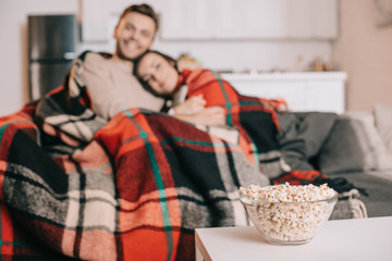 beautiful young couple relaxing on couch and covering with plaid with bowl of popcorn on foreground