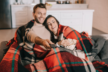 happy young couple watching tv with popcorn on couch and covering with plaid