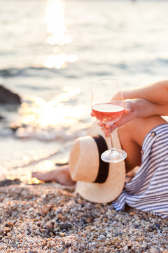 Girl is sitting on sea beach with wineglass of wine at sunset in summer vacation in resort. Tourist woman in striped dress with straw hat is enjoying life, view, traveling, relaxing, drinking.