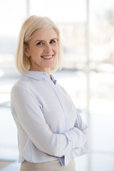 Portrait of smiling positive female office worker or employee standing posing for picture with arms crossed, happy middle-aged businesswoman look at camera making photo at professional photoshoot