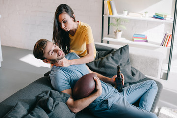angry woman choking her husband while he watching american football on tv at home