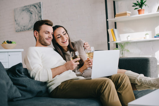 laughing young couple using laptop and drinking wine together on couch at home