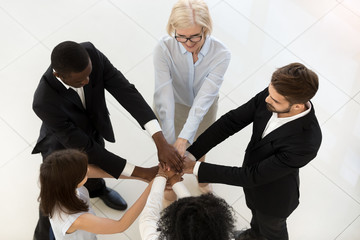 Top view of multiethnic employees stack pile of hands engaged in motivational business training, promise mutual support and help, diverse workers involved in teamwork, show unity at work