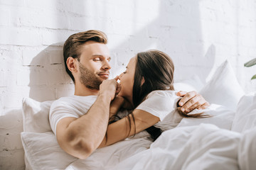 happy young couple relaxing in bed together