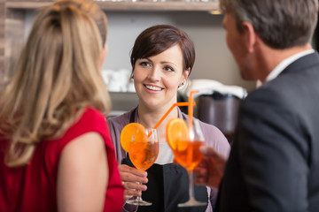 Rear view of woman taking cocktail glass from happy waitress