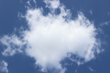 White puffy cloud deep blue sky central formation composition