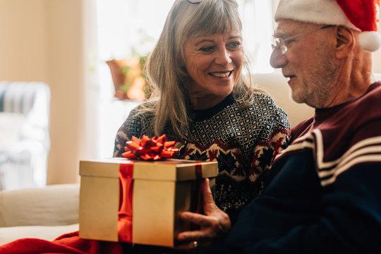 Senior couple sitting at home celebrating christmas holding a gi