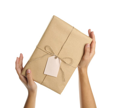 Woman holding parcel wrapped in kraft paper on white background, closeup