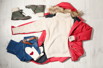 Fototapete - Set of stylish winter outfit on wooden background, flat lay