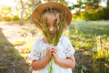 A cute baby girl in a straw hat and white dress is sitting on the grass.