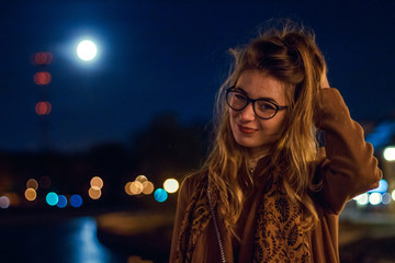 beautiful girl on a city street in the evening in the autumn