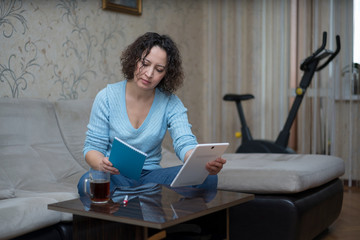 A woman works at home behind a tablet.
