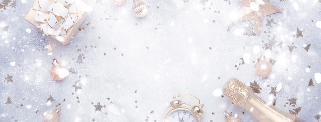 Christmas or New Year composition, frame, gray background with gold Christmas decorations, stars, snowflakes, balls, alarm clock, gift box, glasses and bottle of champagne, banner, top view
