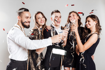 Girls and guys dressed in stylish elegant clothes stand together and clink glasses with champagne on the white background confiture around. Party time
