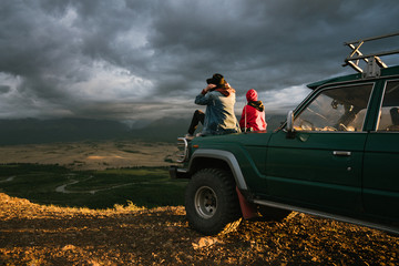 Two anonymous girls sitting on old jeep parked in the wild area surrounded by mountains