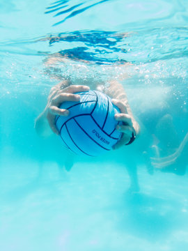 Hands grasping a water polo ball underwater