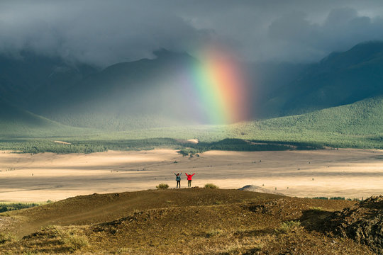 Back view of two yang persons with hands raised in front of mountain landscape with colorful bright rainbow