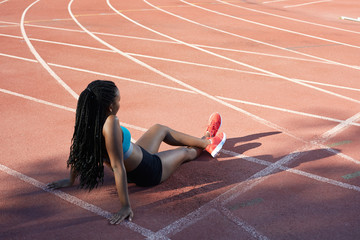 African female athlete sitting and relaxing on the track and field