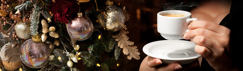 Christmas tree and ball toys with cup of coffee in woman's hands