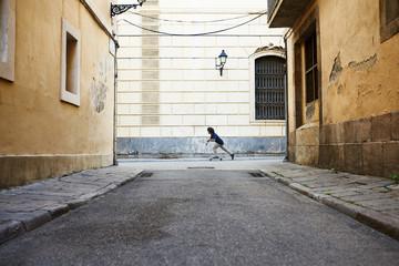 Skateboarder riding his skate in the street.