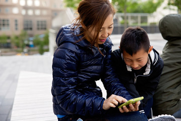Mom and son looking at mobile phone and smiling