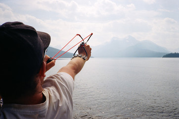 Young man shooting sling shot wrist rocket while camping