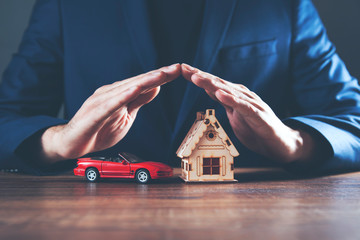 businessman hands house with car model