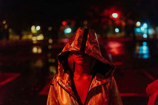 Portrait of woman standing on the streets with red light surroundings
