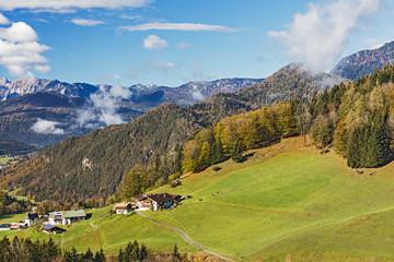 Landschaft mit Bergen, Wäldern und Weiden in den Alpen bei Berchtesgaden in Bayern. Die Gebäude im Vordergrund gehören zu Berchtesgaden, Ortsteil Oberau