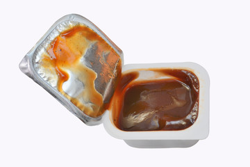 open plastic container with sauce ketchup or a barbecue isolated on a white background