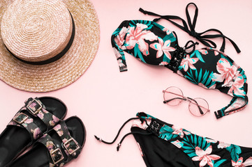 Hat, glasses, swimsuit, flip flops on a pink background. Fashionable girl. Flat Lay. Beach set