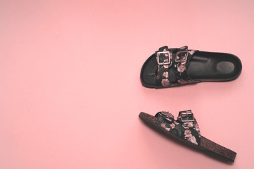 Fashionable leather flip flops with a floral pattern on a pink background