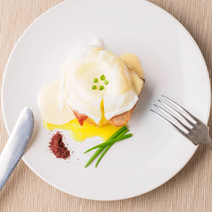 Breakfast is Eggs Benedict - toasted English muffins, bacon, ham, poached eggs, herbs and delicious buttery hollandaise sauce. White plate, knife and fork. Top view . Space for text.