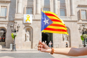 Woman holding Catalan flag against background of the Town City Hall of Catalonia, Barcelona