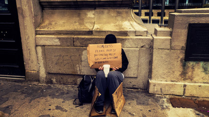 Homeless Person Begging On A Dirty Urban Street in Large City