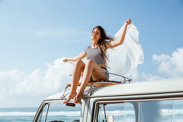 Beautiful woman enjoy road trip nature sitting on the roof