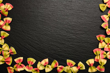 Traditional italian flour product, colored pasta in the form of bow on board, plate or tray of black slate.