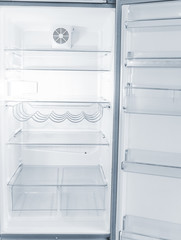 Empty open fridge with shelves in the kitchen at night