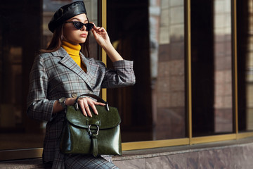 Outdoor fashion portrait of young elegant businesswoman, woman wearing sunglasses, beret, checked suite, blazer, turtleneck, holding green leather bag, posing in street of european city. Copy space Wall mural