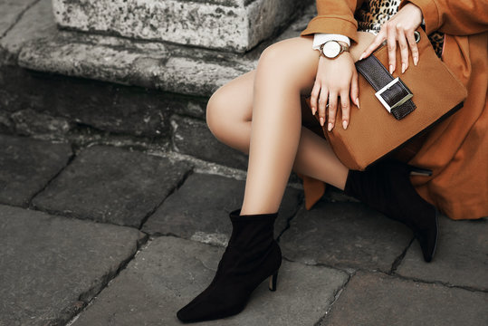 Street fashion details of elegant outfit: woman wearing wrist watch, ankle sock boots, holding light brown, camel color suede handbag, posing in street of european city. Copy, empty space for text