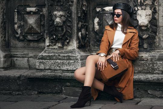 Outdoor full body fashion portrait of  elegant woman wearing glasses, beret, wrist watch,  turtleneck, coat, ankle boots, holding suede handbag, posing in street of european city. Copy, empty space